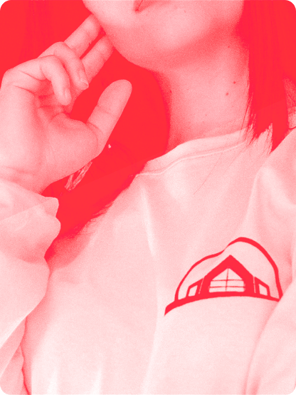Close up image of a young woman wearing a white t-shirt with a red logo of building.