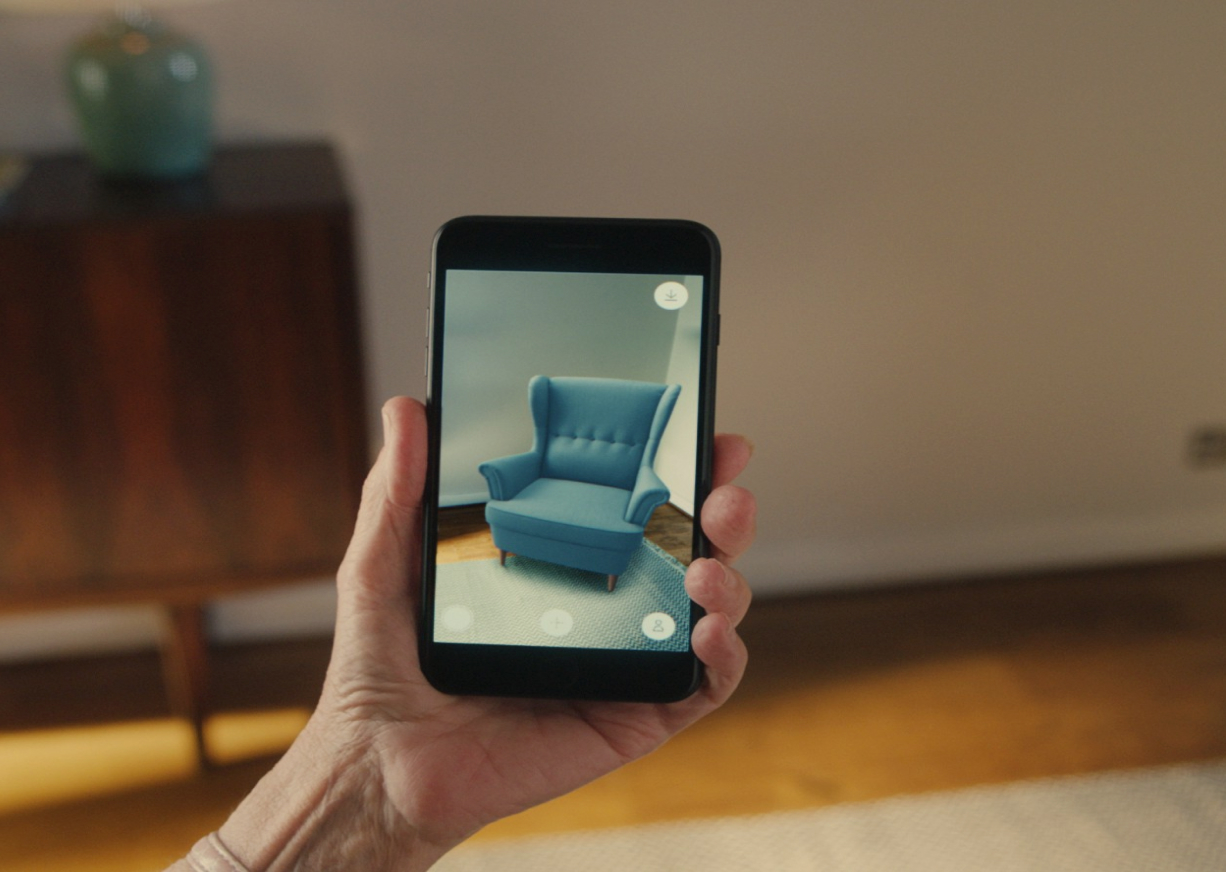 woman holding a phone with a picture of a chair