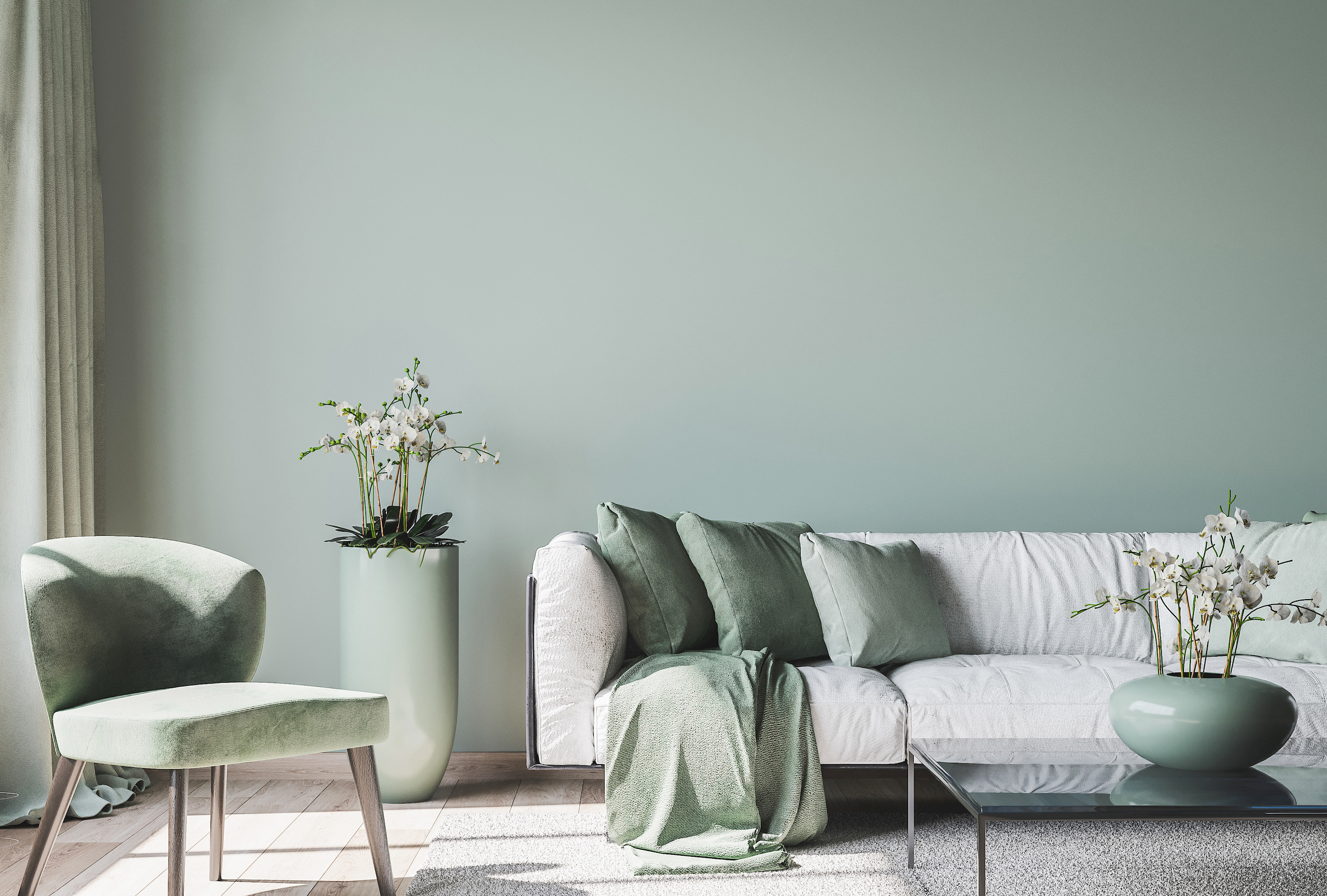 a pastel green room with a white couch