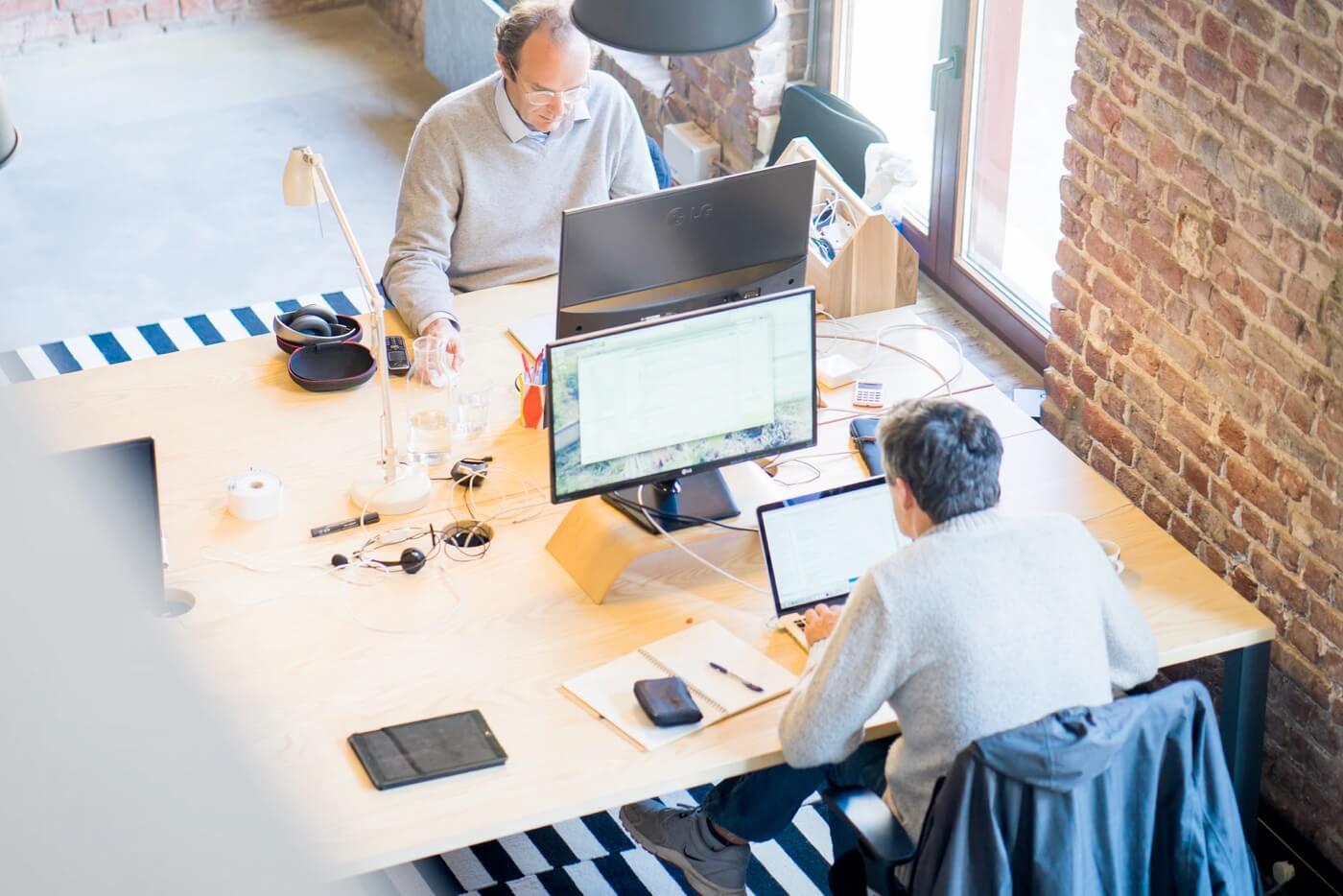 Aufnahme eines Büroarbeitsplatzes von oben. Mann am Arbeiten an einem PC.