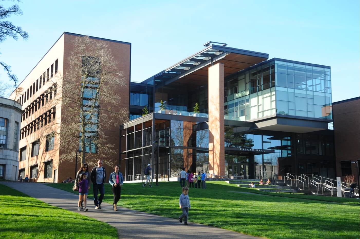 Universitätsgebäude mit Menschen auf Grünflächen.