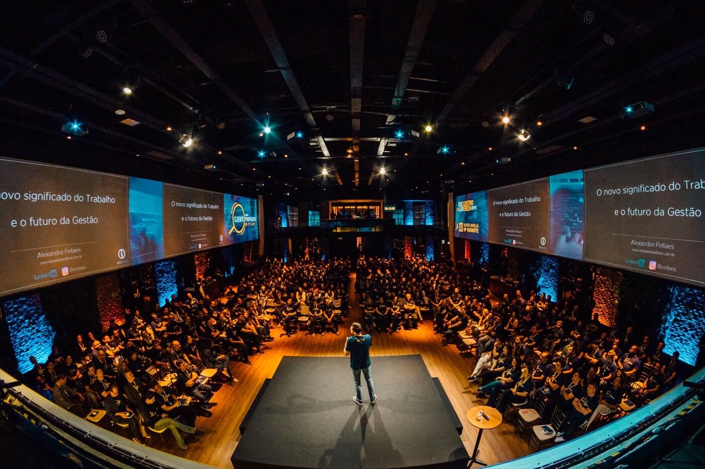 Darstellung eines Speaker Panels mit einer Person auf der Bühne und vielen Zuschauern.