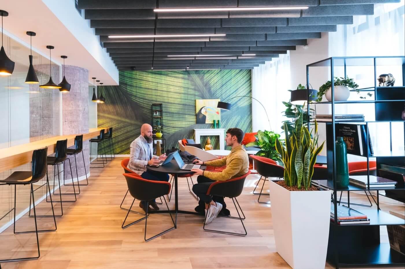 Aufnahme einer offenen modernen Bürofläche mit zwei Personen an einem Tisch.