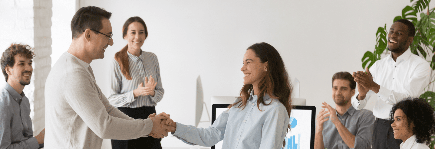 An image of an employee being awarded by her colleagues in front a group of people.