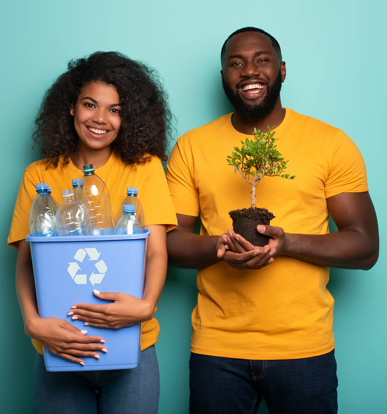 Two people holding plastic bottles and a plant