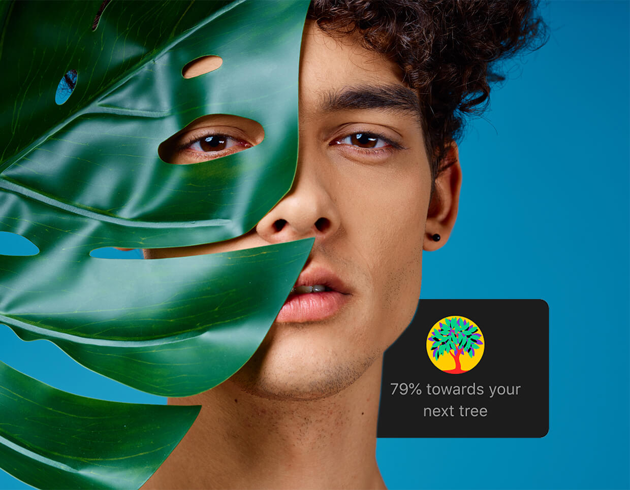 Guy hiding behind a leaf with a planting trees badge