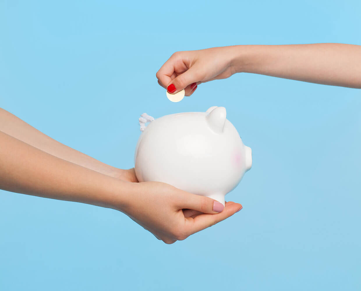 An arm holding a piggy bank and another inserting a coin
