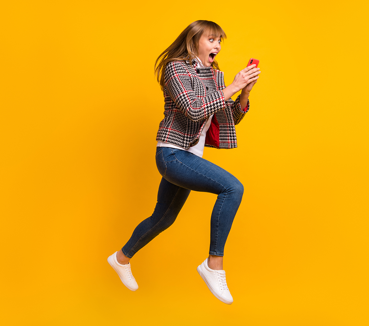 Woman jumping with phone on her hand