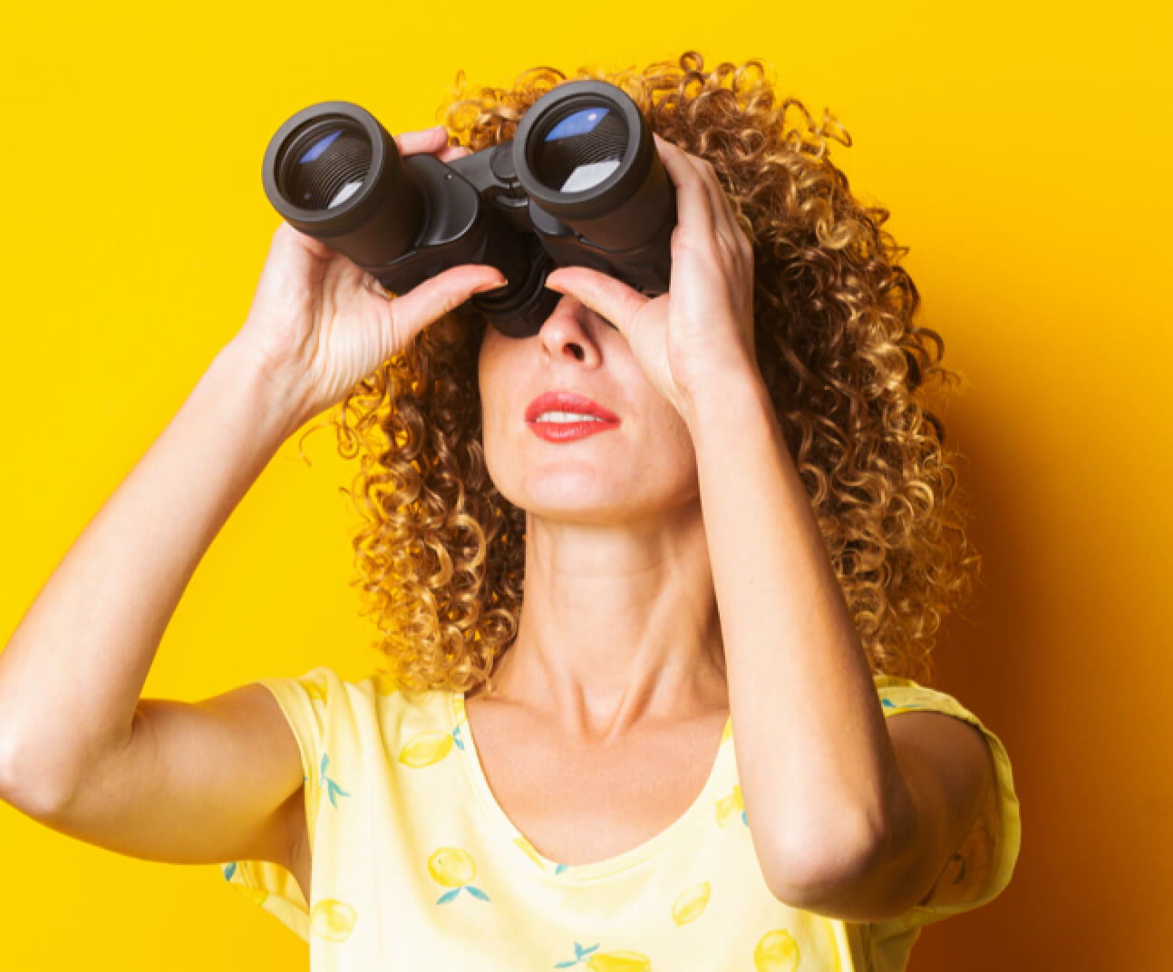 Woman looking out with binoculars