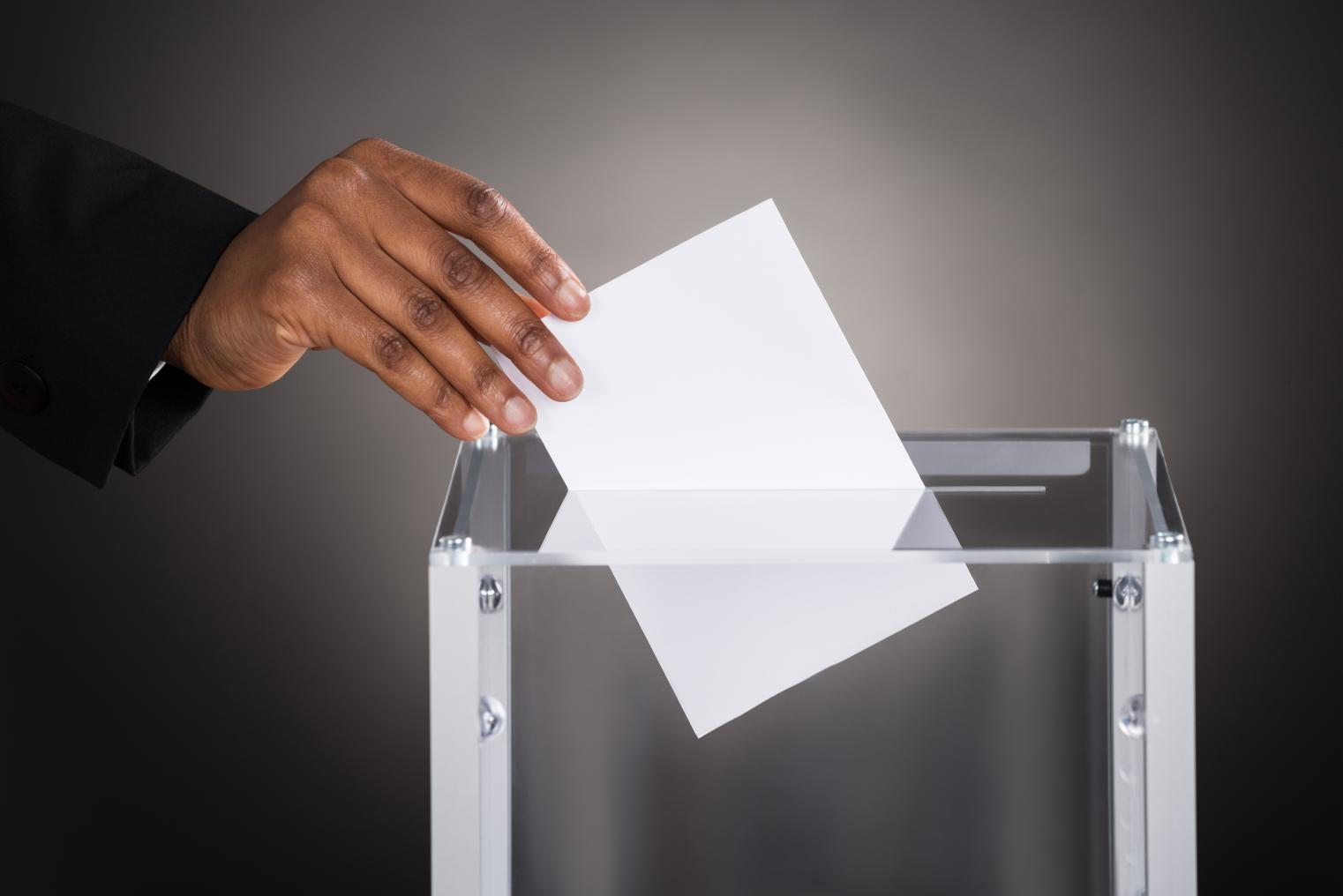 A person placing a ballot into a clear collection box.
