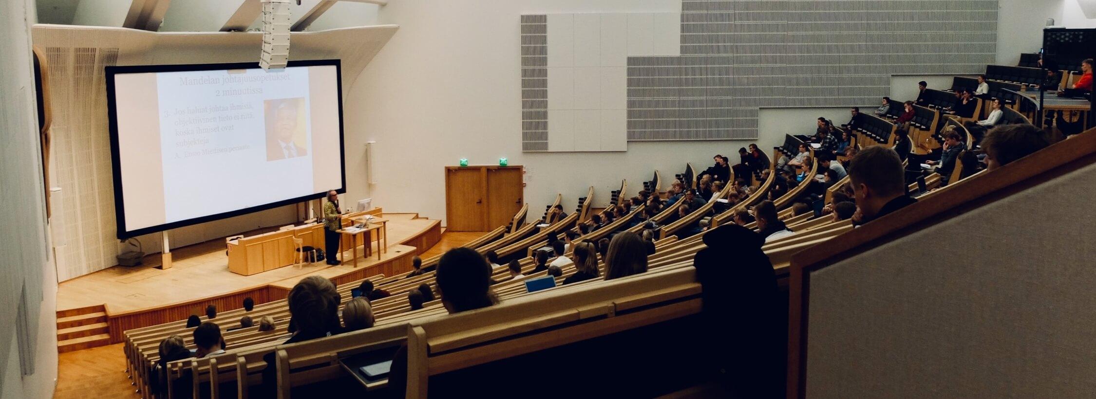 Großer Vorlesungssaal mit Vorlesung und besetzten Stühlen.