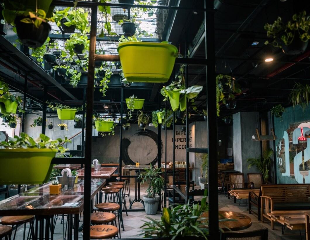 Lounge Bereich in einem Coworking Office mit vielen Pflanzen und Barhockern.