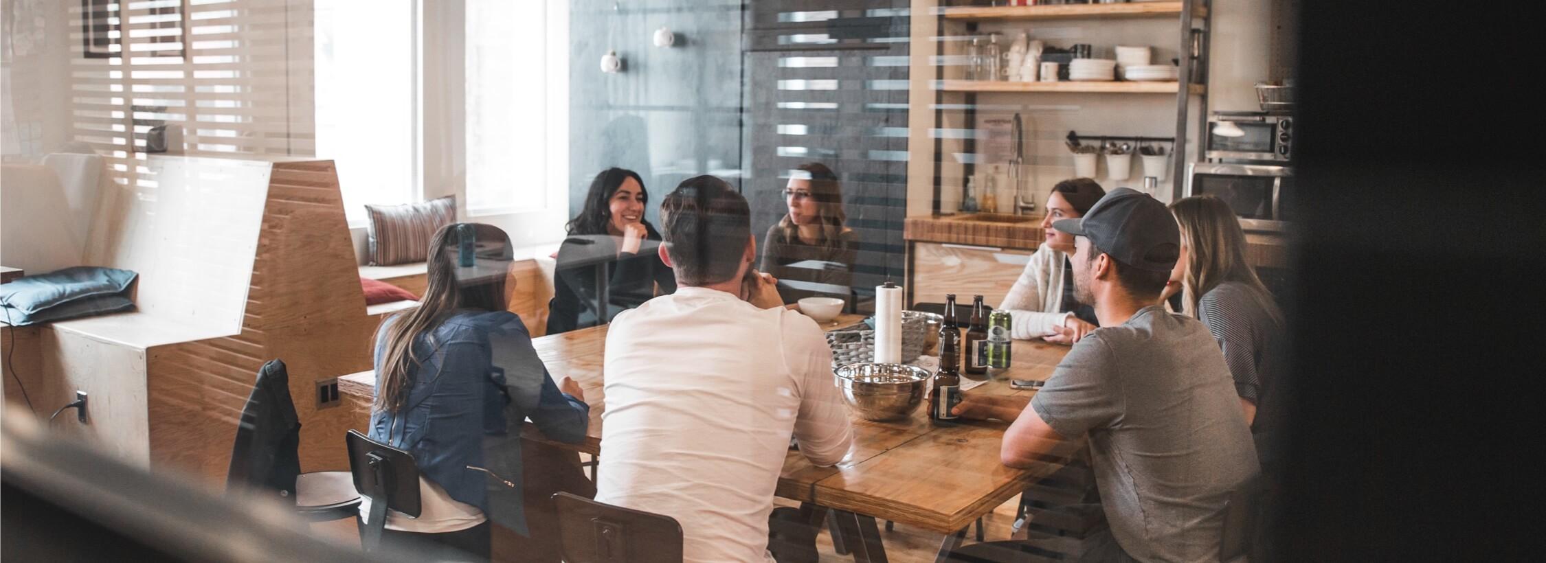 Jugendtreff mit mehreren Menschen um den Tisch.