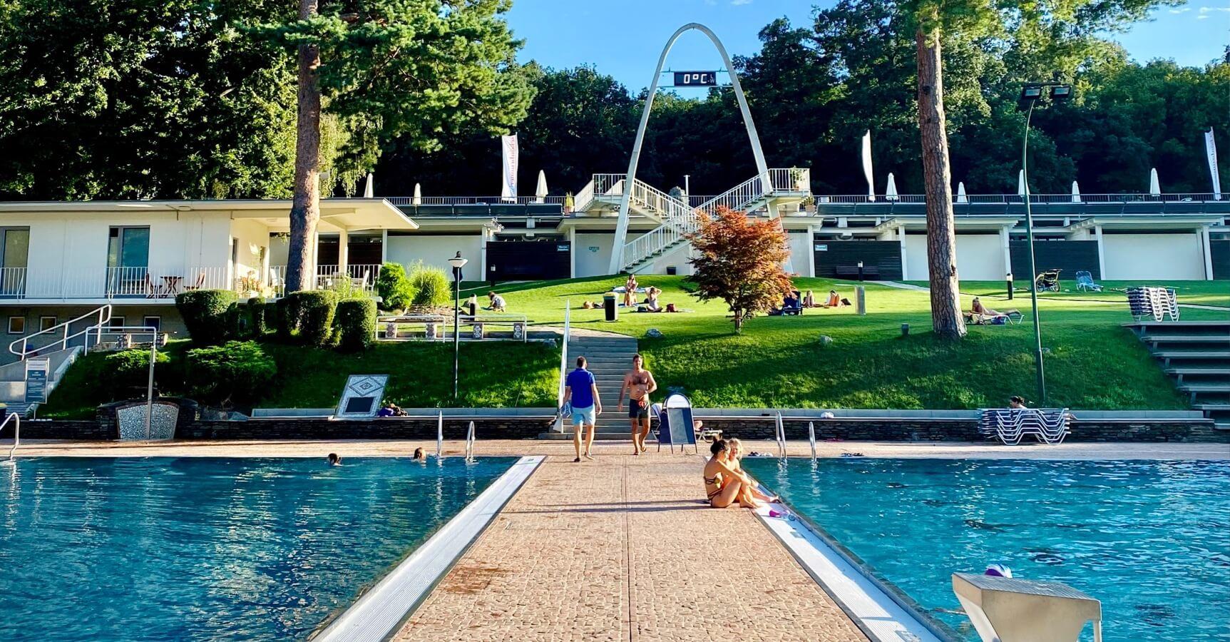 Schwimmbad mit zwei Schwimmbecken sowie Grünflächen.