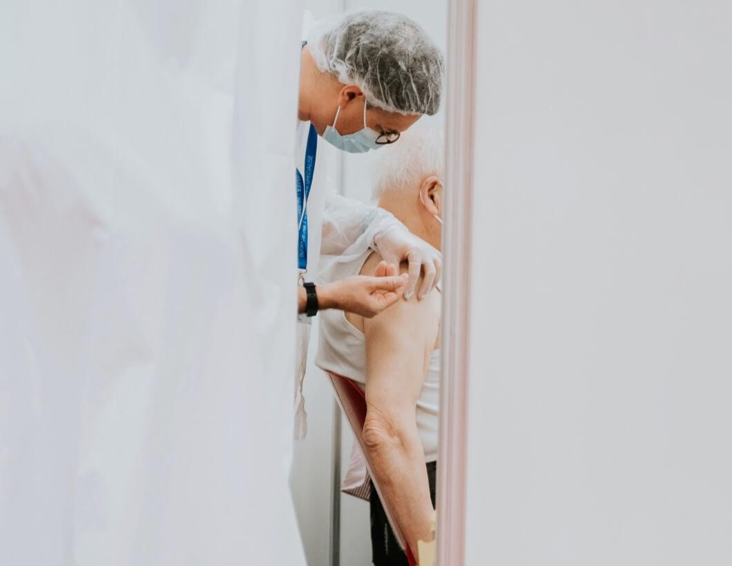 Arzt, welcher gerade einen älteren Patienten impft.