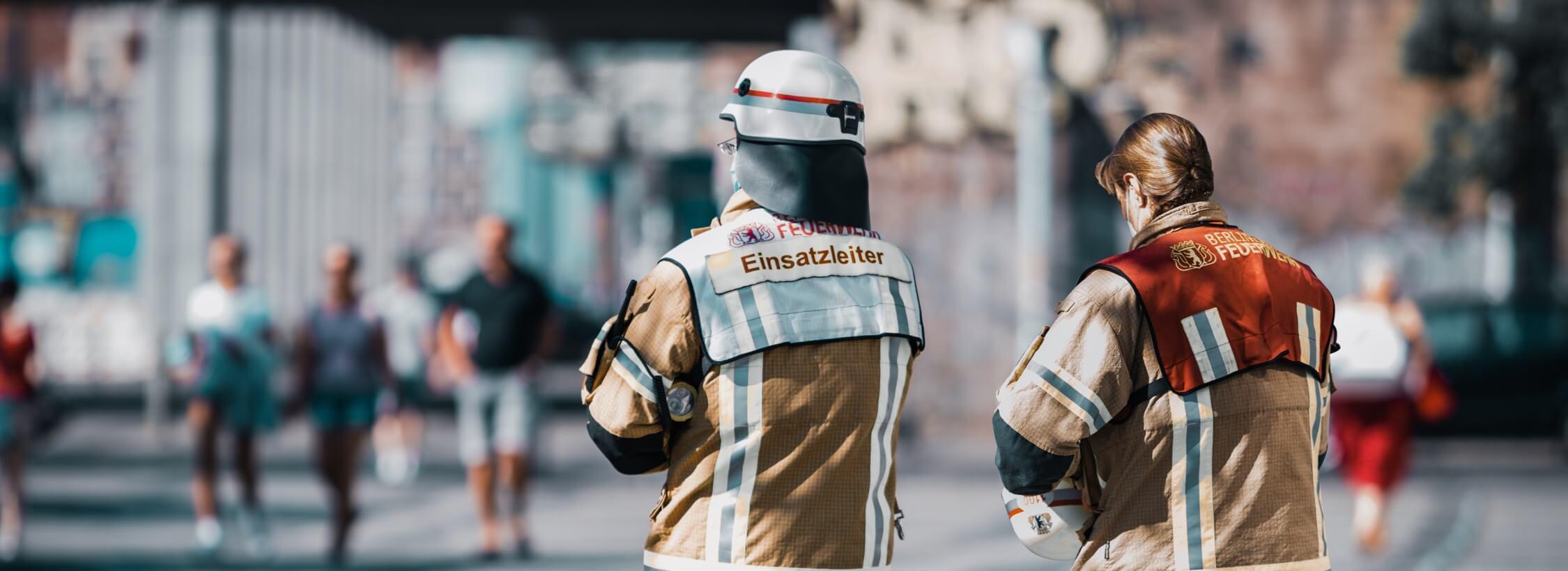 Feuerwehrmann im Einsatz auf Straße von hinten aufgenommen.