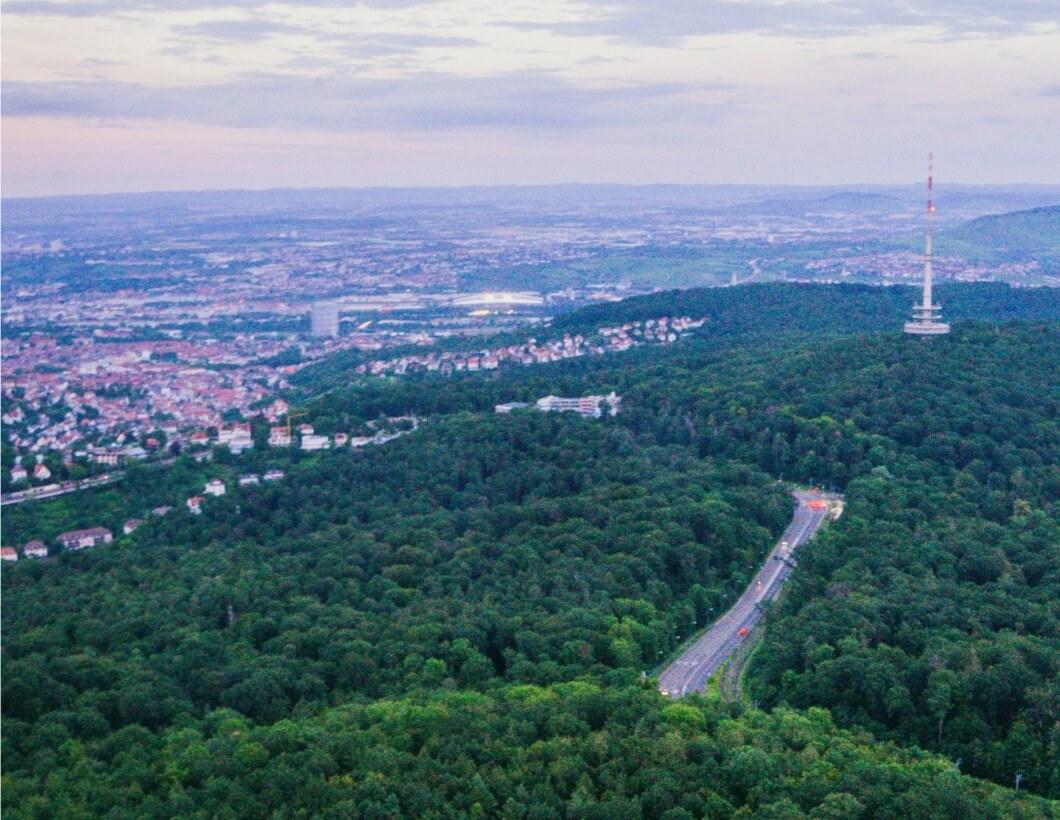 Stuttgart von oben über grüne Waldflächen aufgenommen.
