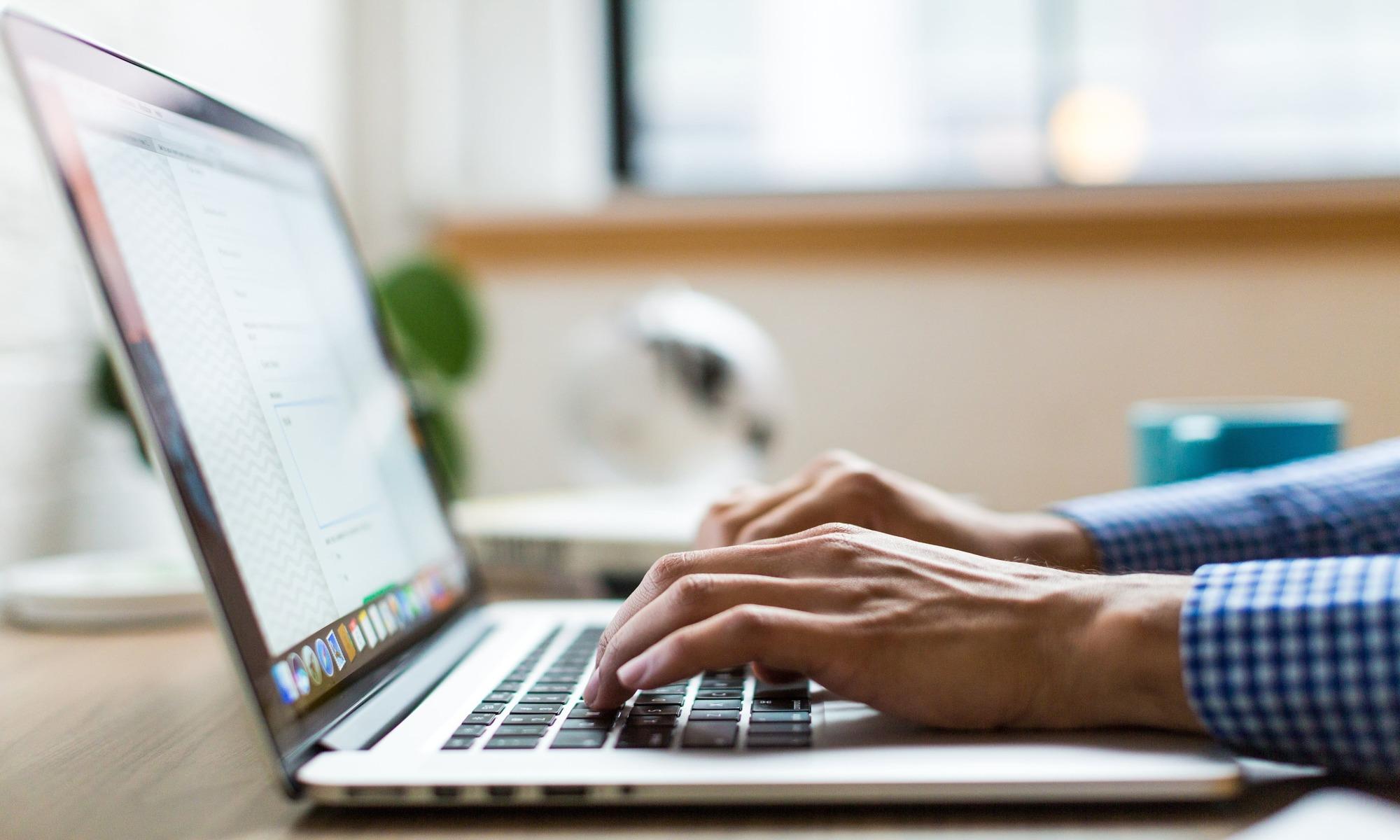 Hände welche auf Laptop schreiben