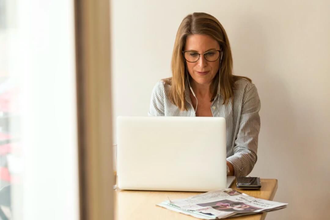 Frau an einem Schreibtisch sitzend im Homeoffice oder in einem Café.