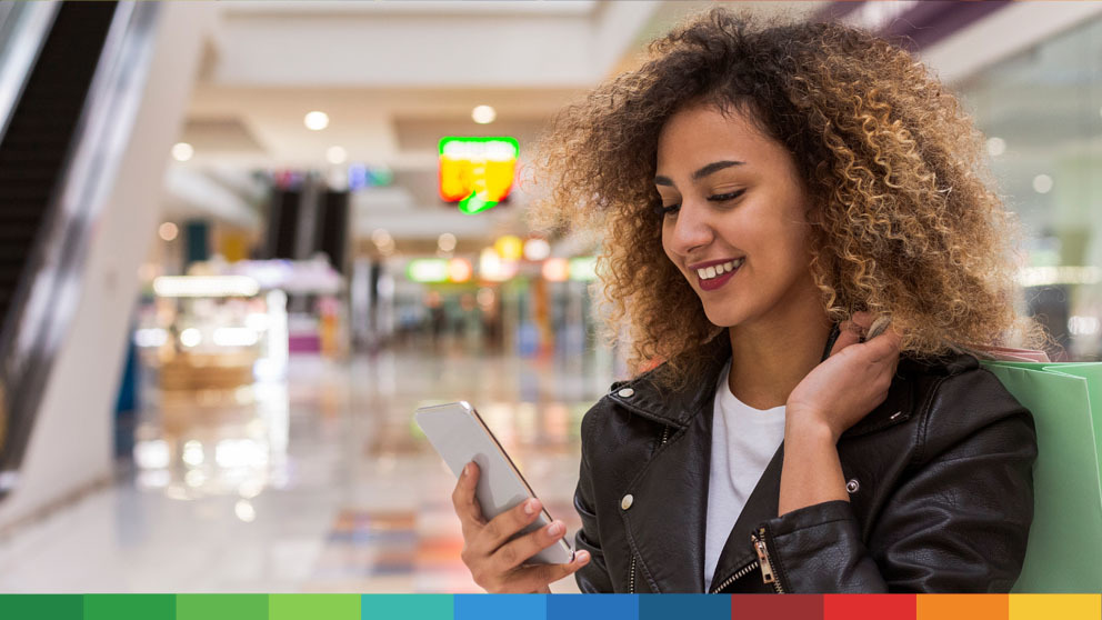 Smiling young woman looking at phone while shopping