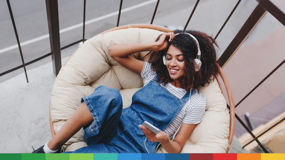 Happy woman relaxing and listening to music on phone
