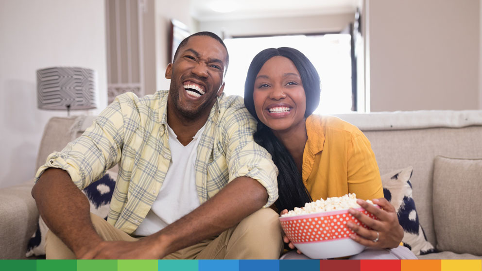 Couple laughing watching a show with popcorn
