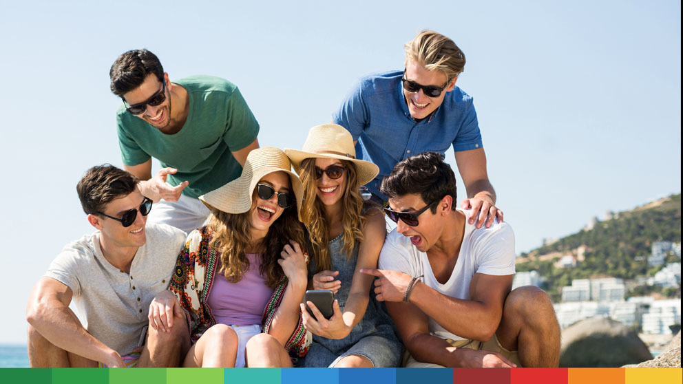 Group of friends looking at phone while traveling