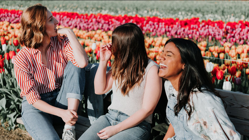 Group of friends laughing in front of a field of flowers