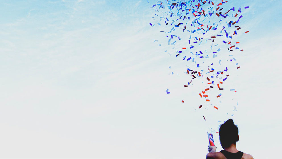Woman shooting confetti into the air