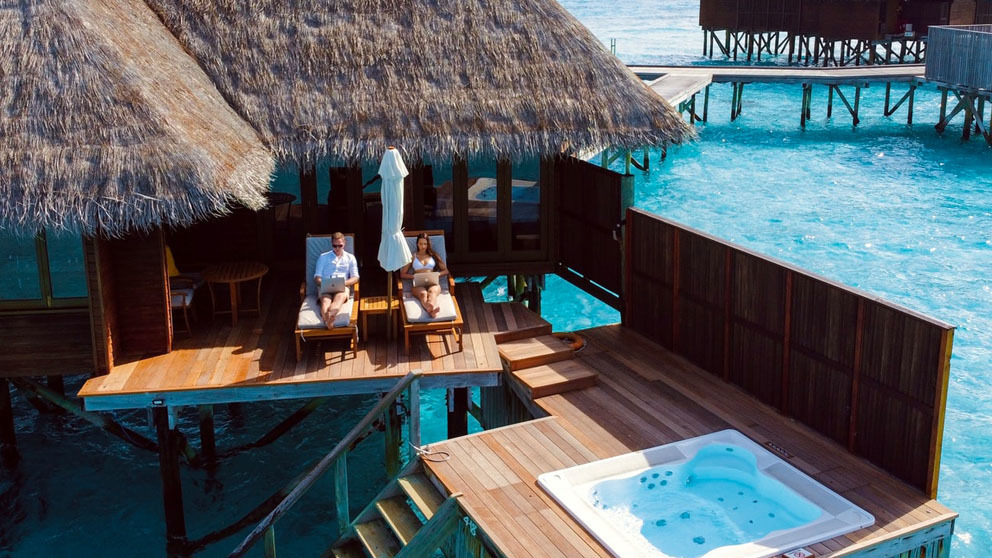 Couple working on laptop in resort with clear blue water