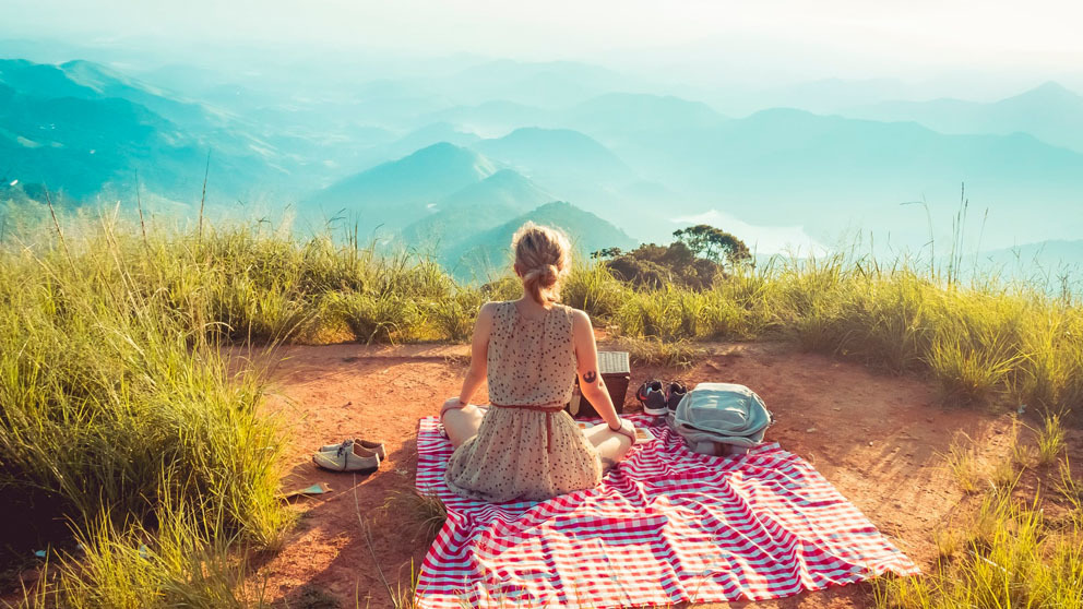Woman picnicking on top of hill