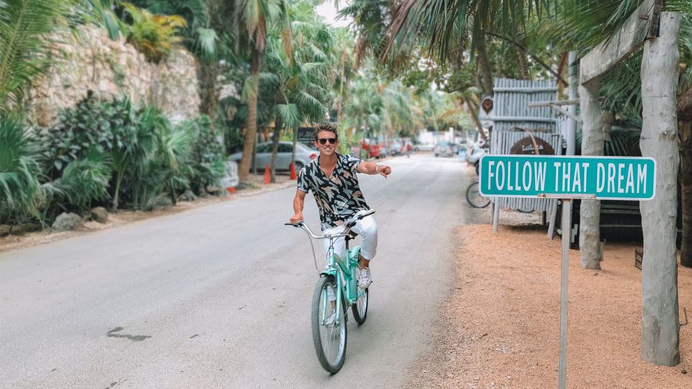 """Man riding his bike pointing to sign saying """"Follow that dream"""""""