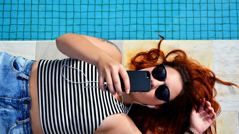 Girl at the border of a pool using her phone and chilling