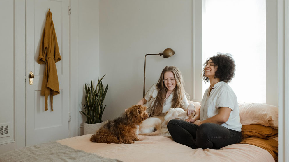 two women sitting on a bed with a dog