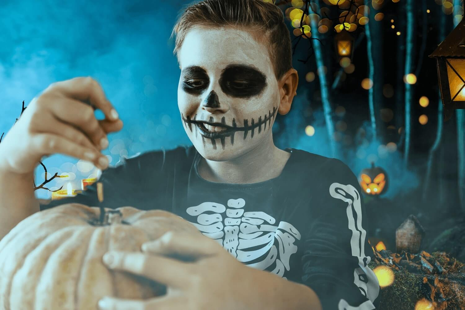 a boy dressed up as a skeleton for halloween carving a pumpkin