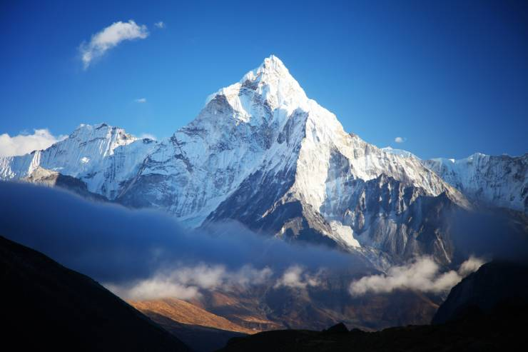 a picture of the snow-covered Himalayas with a bright blue sky and clouds below the mountains
