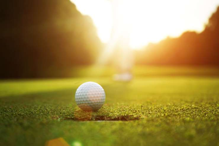 a golf ball sits on the putting green