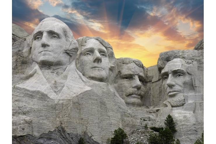Mount Rushmore with sun shining behind and blue skies.