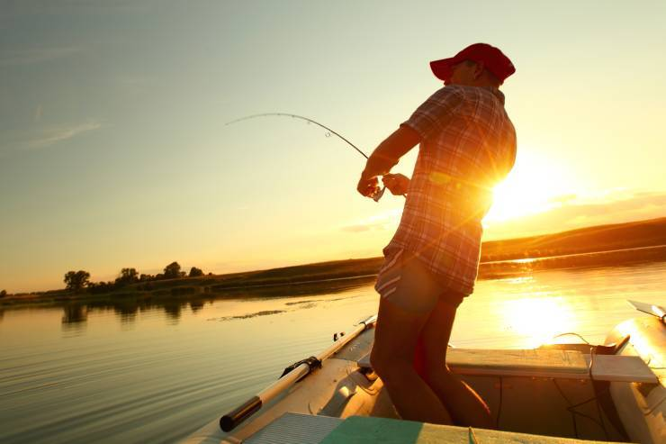 a fisherman on a boat is reeling his catch back in from the lake featuring a sunset