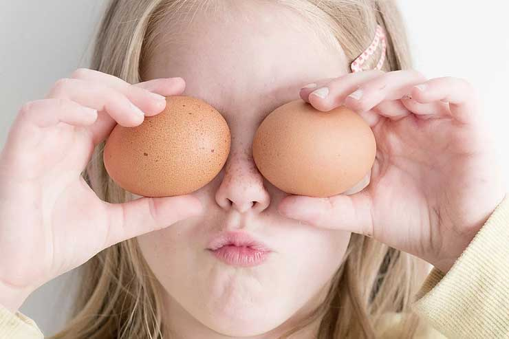 Child holding up two brown eggs up to their eyes