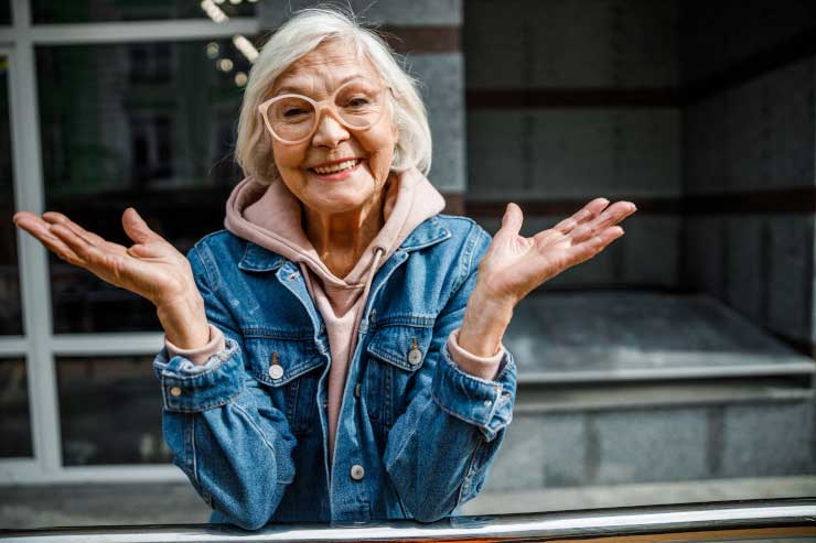 Grandma with peach glasses smiling with hands open extended