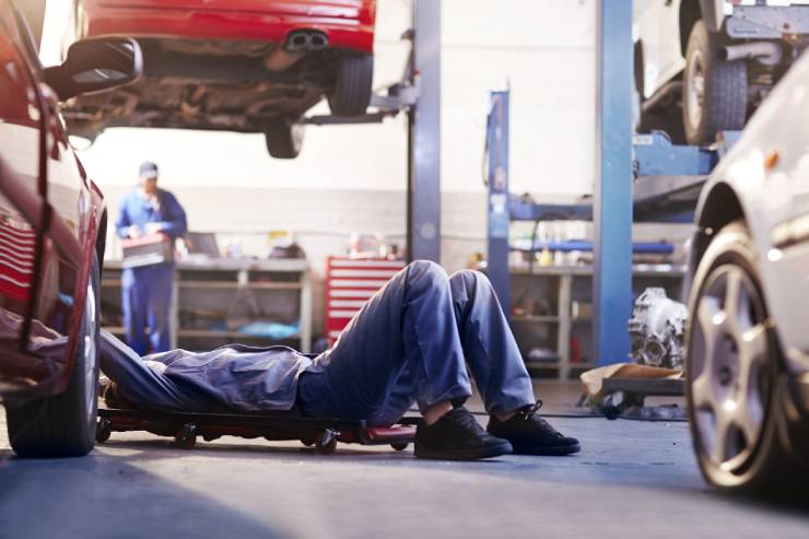 an auto mechanic fixes the undercarriage of a car while on a mechanic's creeper seat