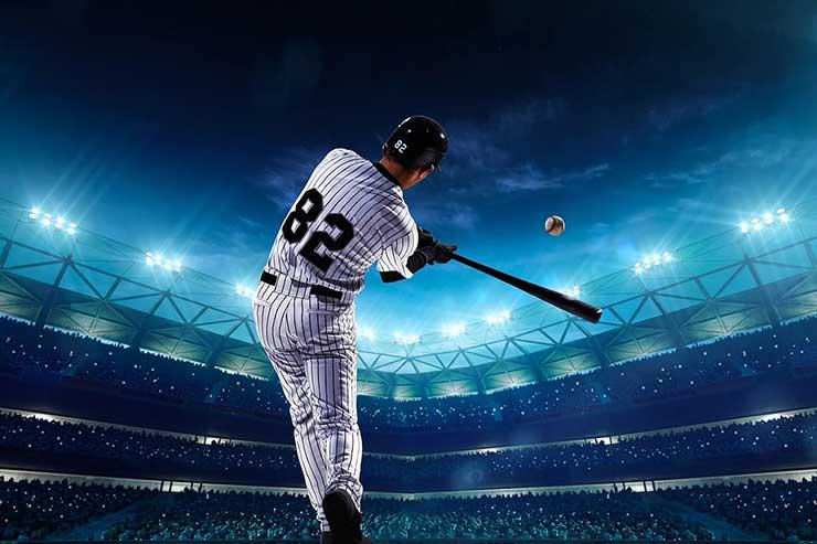 Baseball player hitting ball at a packed baseball stadium at night