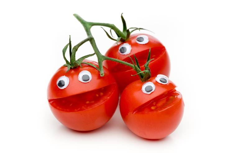 three tomatoes sit bunched together with googly eyes and smiles on them
