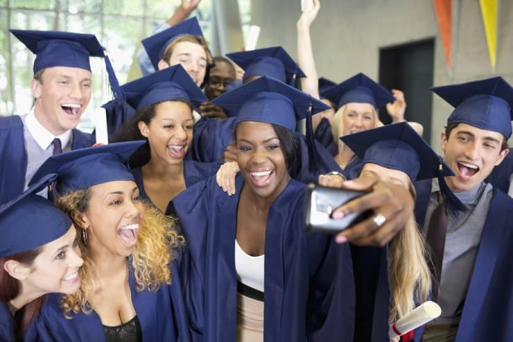 many graduates group together for a celebratory selfie