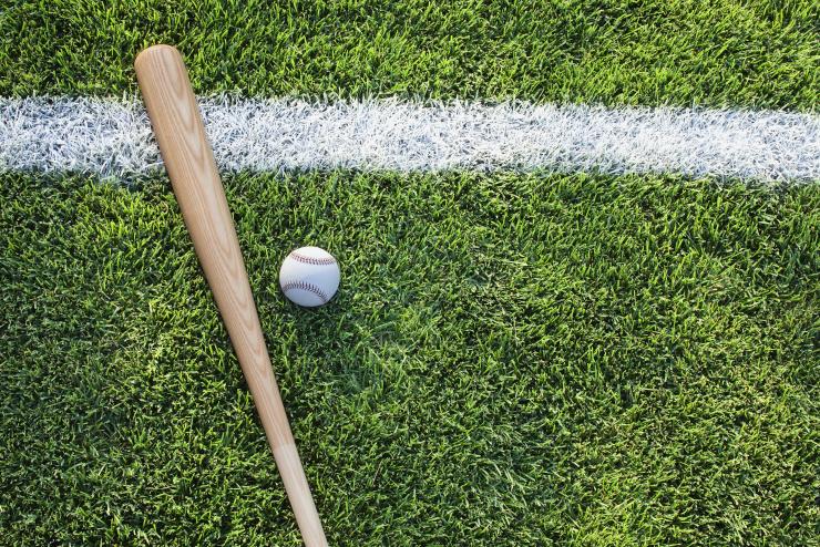 Baseball bat with baseball on the field