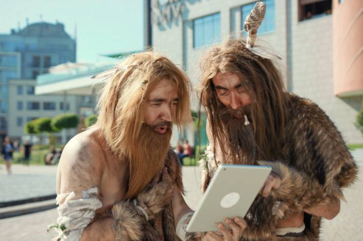 Two cavemen looking at an electronic tablet outside a building.