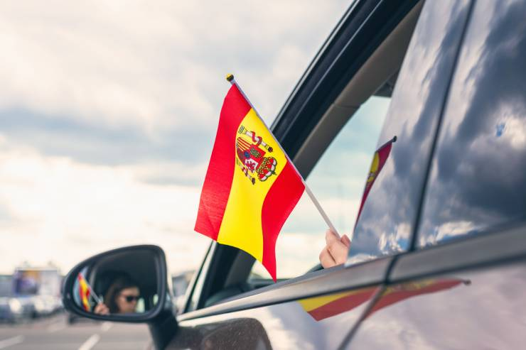 a small Spanish flag is held from a car window