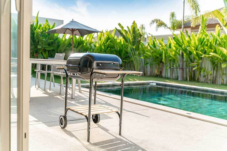 a sleek, silver grill next to a backyard pool surrounded by palm trees