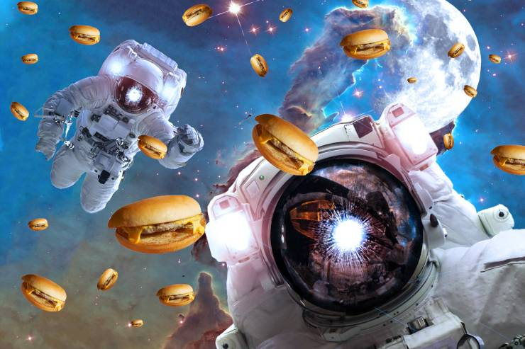 two astronauts float in space surrounded by hamburgers